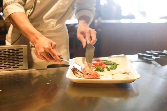 kuvar priprema hranu u restoranu