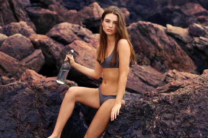 Devojka sedi na steni u kupaćem kostimu