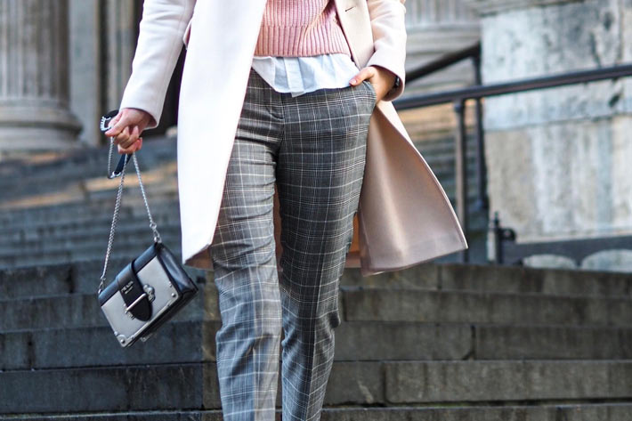 Prikaz žene od struka na dole udevene u karirane pantalone sa 2 torbe u rukama